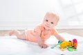 Baby girl  with toy, lying on the floor Royalty Free Stock Photo