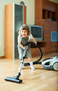 Baby girl with vacuum cleaner on parquet floor Royalty Free Stock Photos
