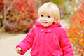 Baby girl walking in fall park bright blonde Stock Photo