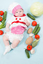 Baby girl  wearing a chef hat with vegetables Stock Photography