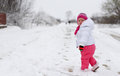Baby girl in wintertime little walking on the road with snow Stock Photo
