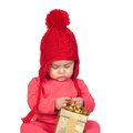 Baby girl with wool hat looking a gift Royalty Free Stock Photos