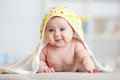 Baby girl wrapped towel in children nursery room. Newborn kid relaxing in bed after bath or shower. Royalty Free Stock Photo