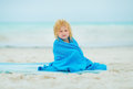 Baby girl wrapped in towel sitting on beach Royalty Free Stock Photo