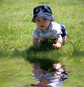 Baby in the Grass by Water Stock Photos