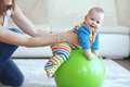 Baby gymnastic playing with ball with mother at home Stock Image