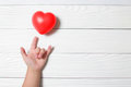 Baby hand supporting with a red heart. Royalty Free Stock Photo