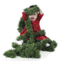 Baby happily tangled in garland an adorable dressed up girl christmas on a white background Stock Photography