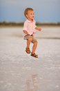 Baby in a happy jump little boy jumping with joy on the face of summer day on the nature of the water Royalty Free Stock Photography