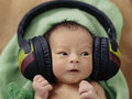 Baby with headphones a tiny newborn wearing large rasta colored Royalty Free Stock Photo