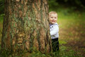Baby hiding behind tree in park Royalty Free Stock Photo