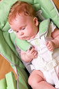 Baby in high feeding chair Stock Image