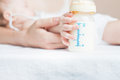 Baby holding a baby bottle with breast milk Royalty Free Stock Photo
