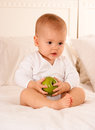 Baby holding a green apple cute on bodysuit Royalty Free Stock Image