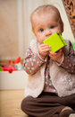 Baby holding a green block facing Stock Photography