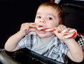 Baby with large candy cane little toddler tries to eat a red and white striped but the wrapper is still on Royalty Free Stock Photography