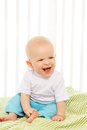 Baby laugh in his crib boy sitting with Stock Photo