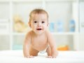 Baby laughing, creeping and playing in nursery Royalty Free Stock Photo