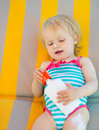 Baby laying on sun bed with sun block bottle Stock Image
