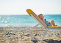 Baby laying on sunbed on beach Royalty Free Stock Photography