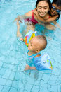 Baby learn to swim with mom Stock Photos
