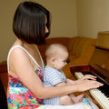 Baby is learning to play the piano Stock Photography
