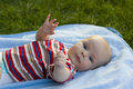 Baby lies on a back cover outdoors Stock Image