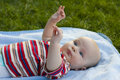 Baby lies on a back cover outdoors Royalty Free Stock Images
