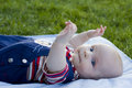 Baby lies on a back cover outdoors Stock Photo