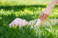 Baby lies grass spring park mother hand touches him Royalty Free Stock Photography