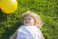 Baby lies on a grass in sunny day Royalty Free Stock Images