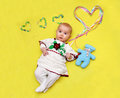 Baby lies and holds a big heart in his hands, love Royalty Free Stock Photo