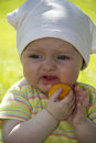 Baby little eats an apricot in the garden Royalty Free Stock Photos