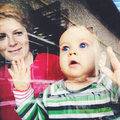 Baby looking through window mother and girl house Stock Image