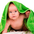 Baby looks out curious little from under a green towel Stock Photography