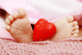 Baby love adorable newborn feet holding a red heart Stock Image