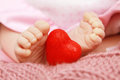 Baby love adorable newborn girl holding a heart with her foot Royalty Free Stock Photography