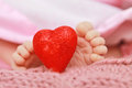 Baby love a red heart with adorable newborn feet in the background depict the beautiful for babies background of soft pink Stock Photography
