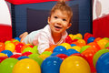 Baby lying in colorful balls smiling boy inside a playpen Royalty Free Stock Images