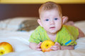 Baby lying and holding a yellow apple Royalty Free Stock Photo