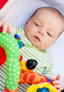 Baby lying in pram with toy Stock Photo