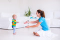 Baby making his first steps cute little boy walking to mother in a white sunny living room Stock Photography