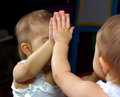 Baby and mirror looking a with oneself reflection Stock Photography