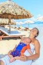 Baby and mom are relaxing on sunbed Stock Photos