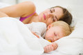 Baby and mother sleeping together in bed Stock Photography