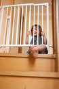 Baby near safety gate small approaching of stairs Stock Photos