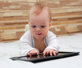 Baby with new tablet pc touching black computer Stock Image