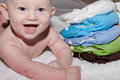 Baby next to a stack of cloth diapers happy smiling lying all in one Royalty Free Stock Image