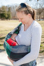 Baby nursing in sling mom her during a walk the park on a sunny day Stock Photo