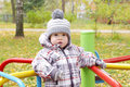 Baby outdoors in autumn on playground age of year plays standing carousel Stock Photography